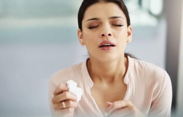 une femme victime d'alergie aux acariens éternue