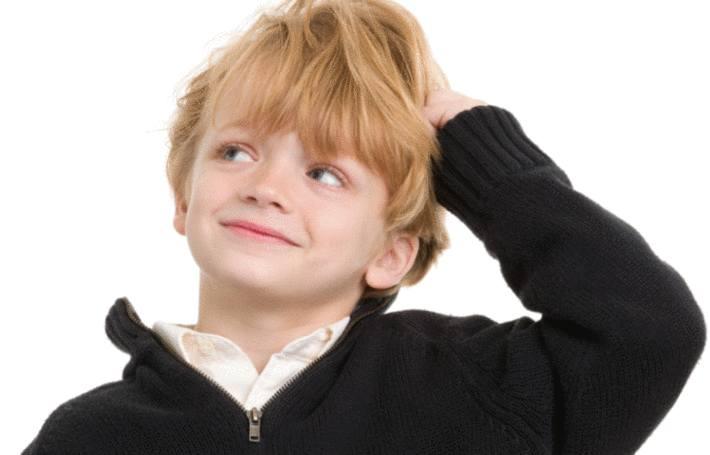 un petit garçon habillé d'un pull over noir se gratte la tête
