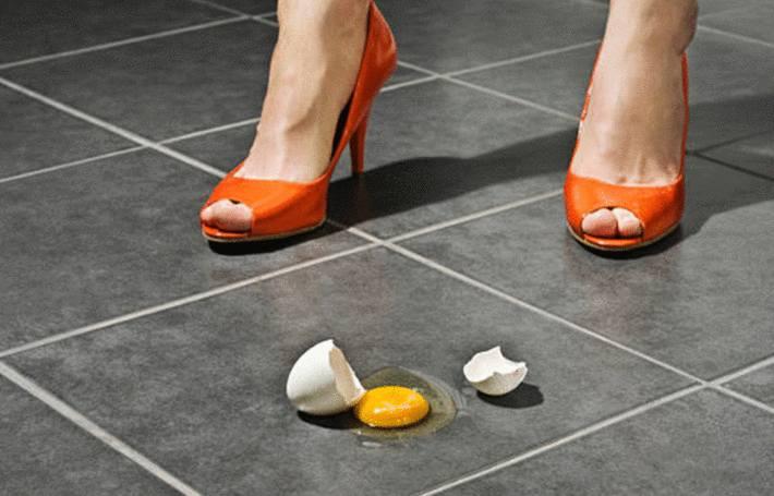 chaussée de talons hauts orange une femme a fait tombé un oeuf sur un sol ardoise