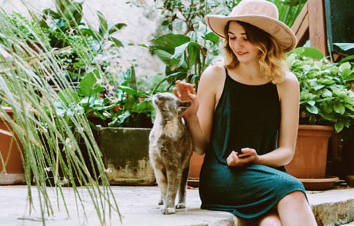 une femme qui caresse un chat sur une terrasse en pierre