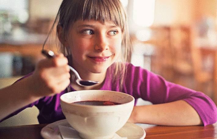 une petite fille déguste un borchtch