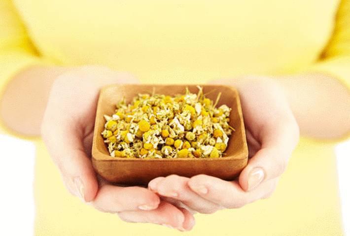 une femme en jaune tend un bol de camomille séchée