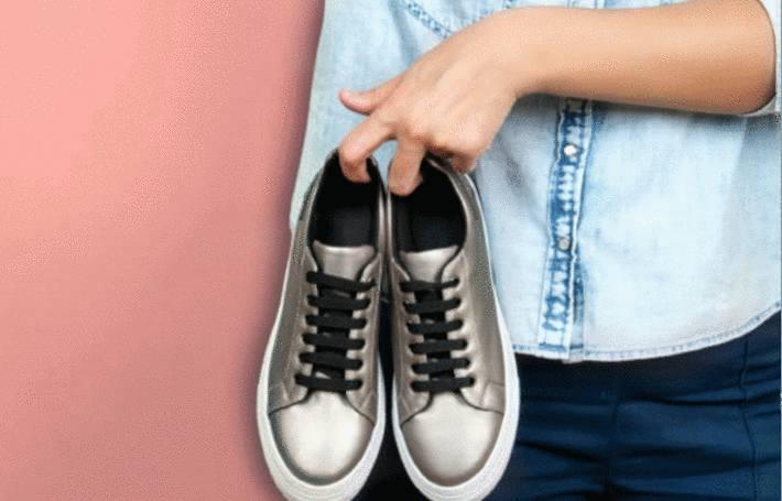 quelqu'un tend une paire de chaussures
