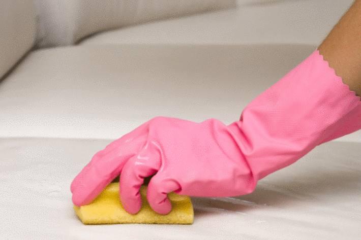 une main sous un gant en plastique rose enleve une tache avec une éponge sur un canapé blanc