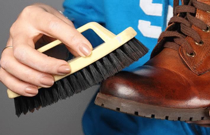 une main d'homme brosse des chaussures