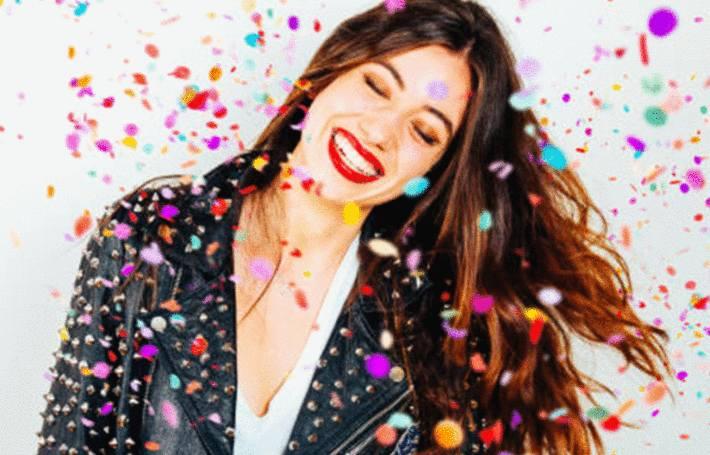 une femme brune reçoit sur elle quantité de confettis multicolore