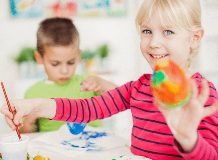 une petite fille montre un oeuf de paques qu'elle vient de décorer