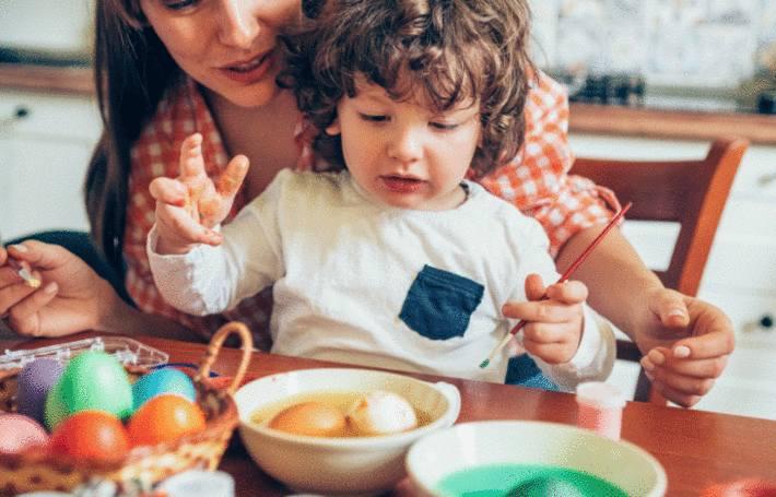 une mère et son enfant colorent des oeufs de paques