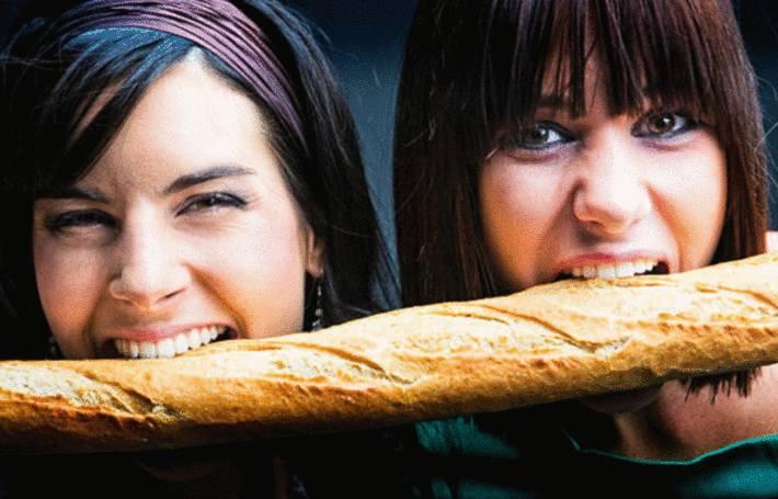 2 jeunes femmes mordent dans la même baguette de pain