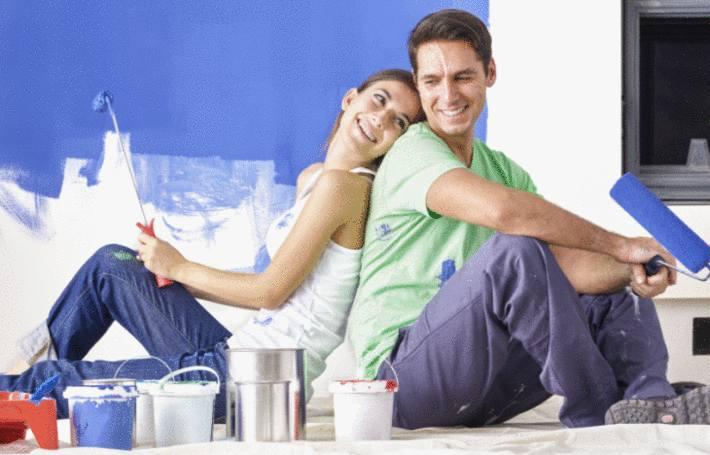 un couple se repose assis alors qu'ils sont en train de peindre des murs