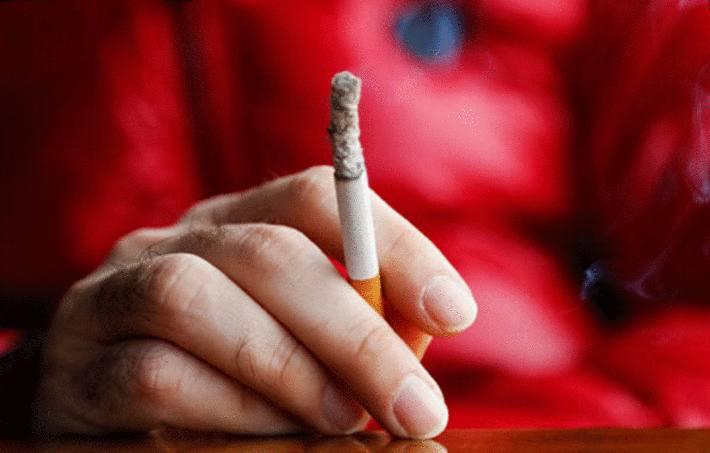 quelqu'un en rouge fume une cigarette
