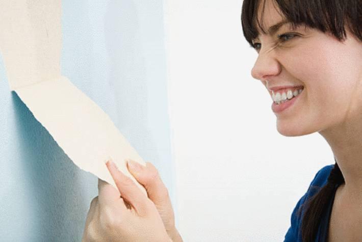 une femme enlève du papier peint
