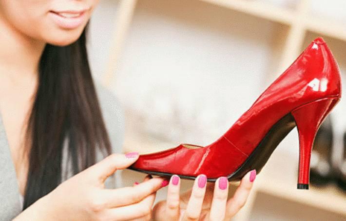 une femme a dans ses mains une chaussure rouge en cuir verni