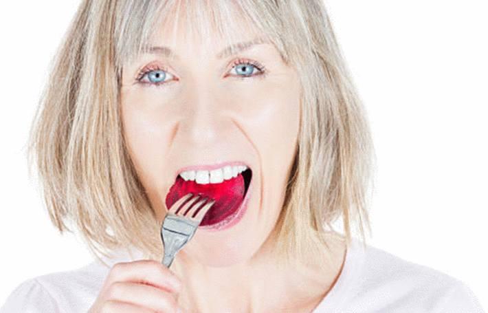 une femme mange un morceau de betterave