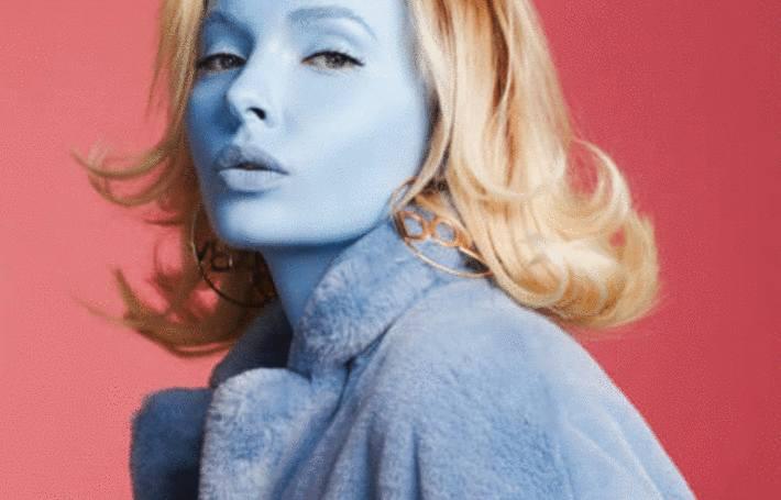 sur fond rose une femme au visage bleu qui porte un manteau en imitation fourrure bleu ciel