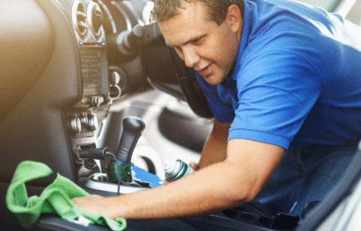 un homme nettoie son siège voiture avec un chiffon bleu