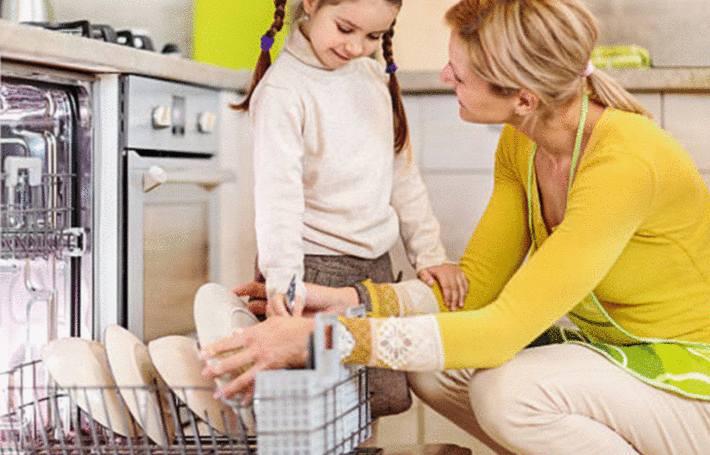 une mere explique à sa fille comment nettoyer le lave-vaisselle