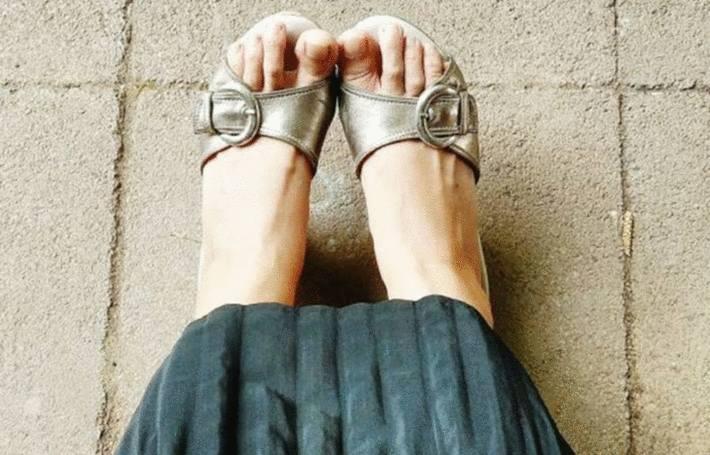 sur un sol ciment ou béton des pieds de femme chaussées de sandales argent