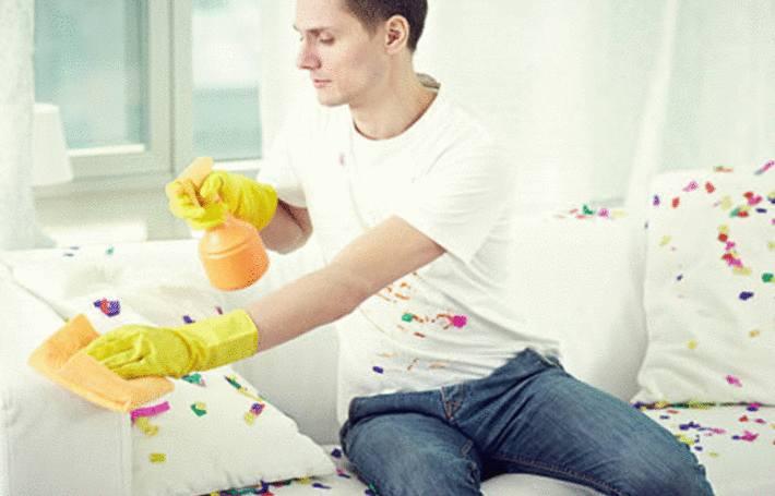 un homme enlève une tache de gras sur un canapé en tissu