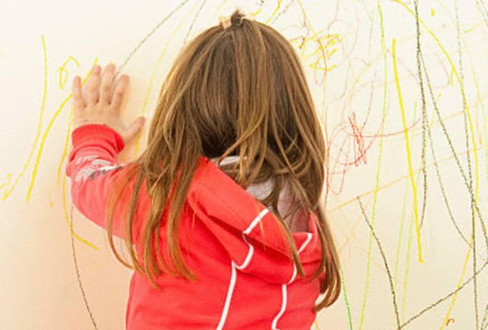 une petite fille dessine sur un mur peint