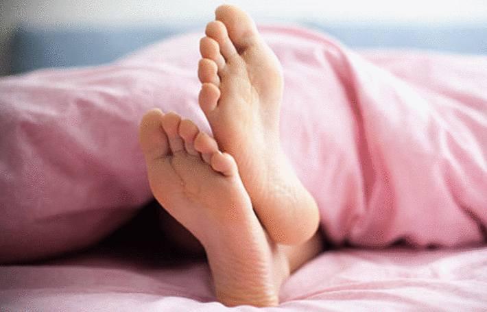 dans un lit, des pieds sortent dessous une couette rose