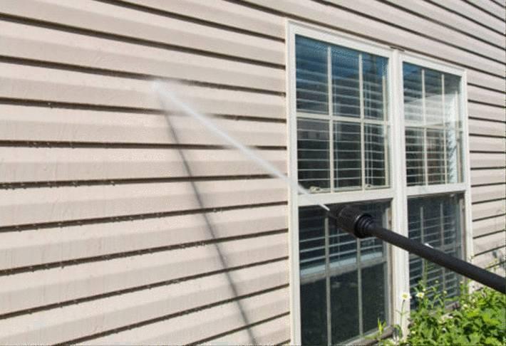 quelqu'un nettoie la façade d'une maison