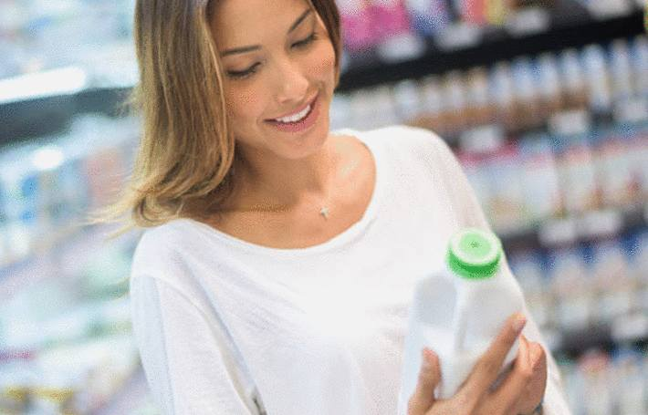 une femme blonde examine une bouteille de lait de soja