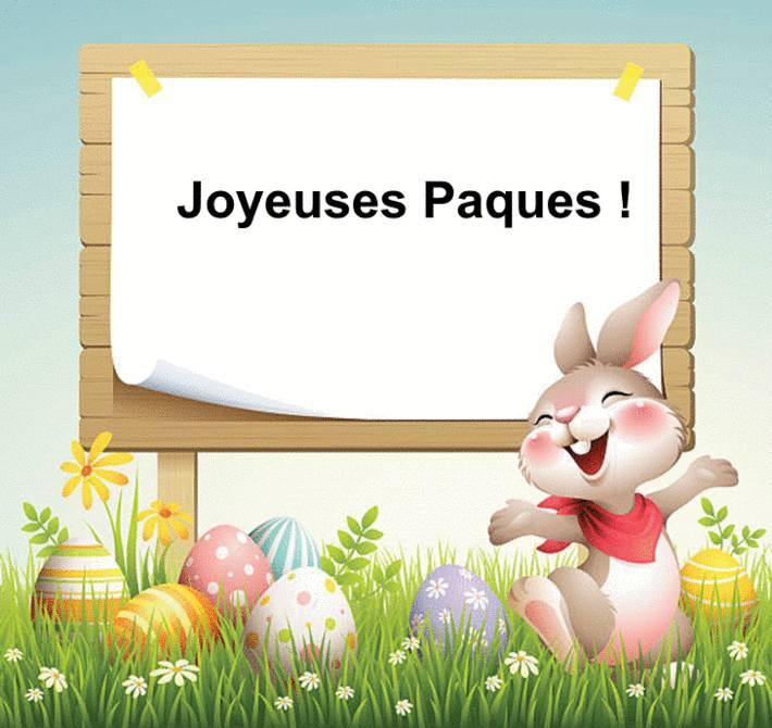 Devant un lapin joyeux, sur l'herbe, au milieu d'oeuf de paques, sur un panneau est écrit joyeuses paques