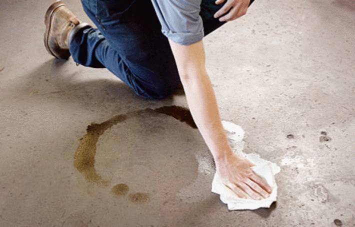 un homme enleve une tache d'essence sur le sol du garage