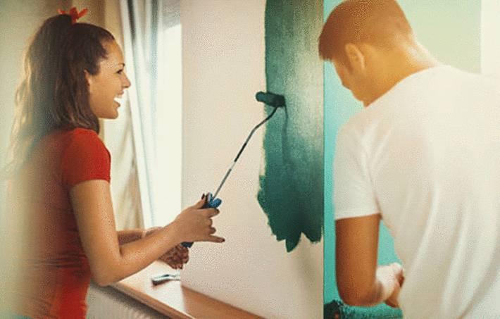 une femme peint un mur avec un rouleau tandis qu'un homme la regarde
