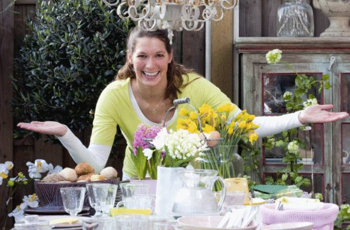une femme montre la table qu'elle a dressé à l'occasion du déjeuner de paques