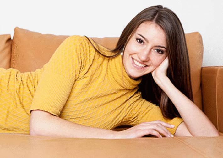 une femme est allongée sur un canapé en cuir