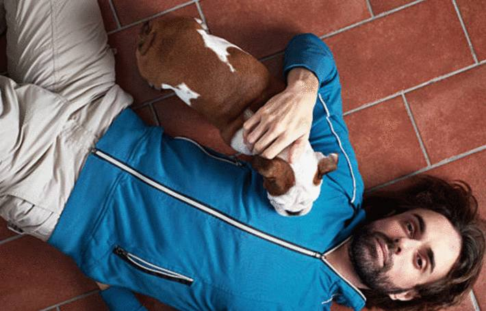 un homme avec un chiot dans les bras est allongé sur un sol en tomettes