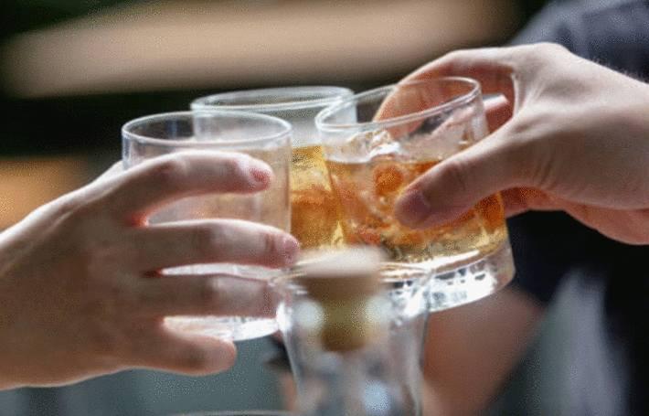 des personnes boivent du whisky, et choquent leur verre