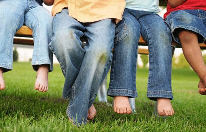des enfants aux jeans tachés d'herbe