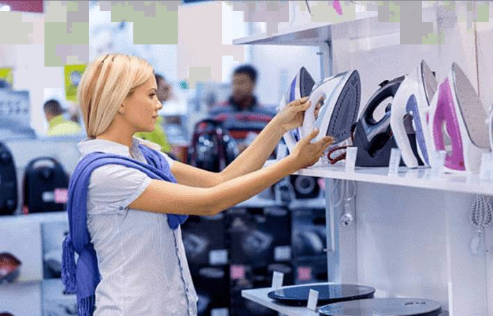 femme-blonde-examinant-un-fer-à-repasser-sur-une-étagère-de-fers-à-repasser-dans-un-magasin-d-électroménager