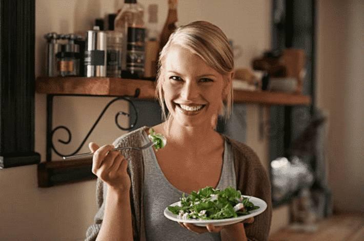 femme-blonde-souriante-mangeant-de-la-salade-verte.