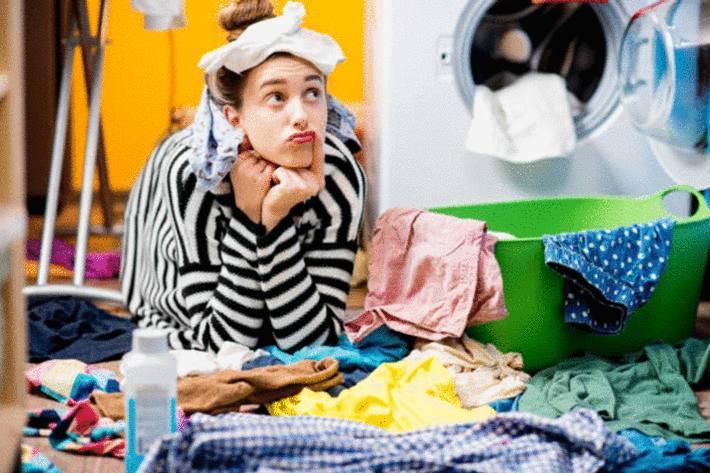 femme-brune-perplexe-avec-du-linge-sur-la-tête-au milieu-d-un-tas-de-linge-devant-son-sèche-linge-en-arrière-plan