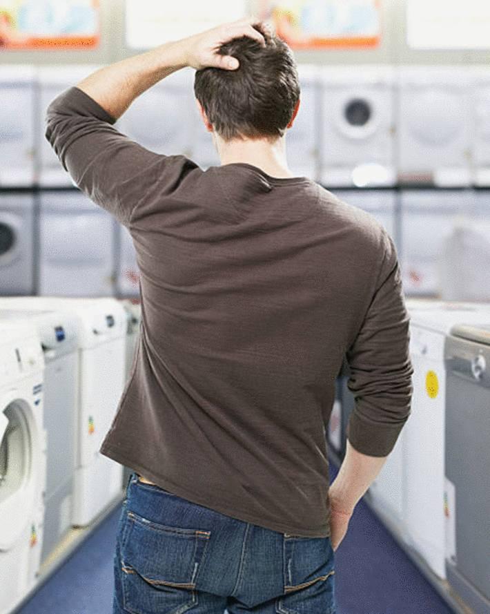 homme-brun-de-dos-se-grattant-la-tête-face-au-rayon-des-machines-à-laver