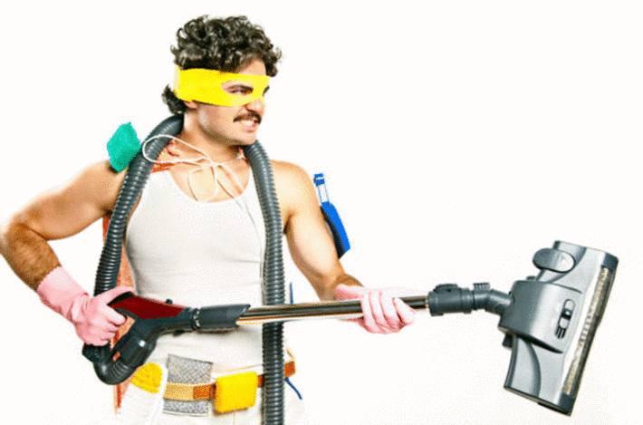 homme-déguisé-en-super-héros-tenant-un-aspirateur-comme-un-fusil-avec-des-brosses-à-aspirateur-autour-du-cou-et-de-la-taille
