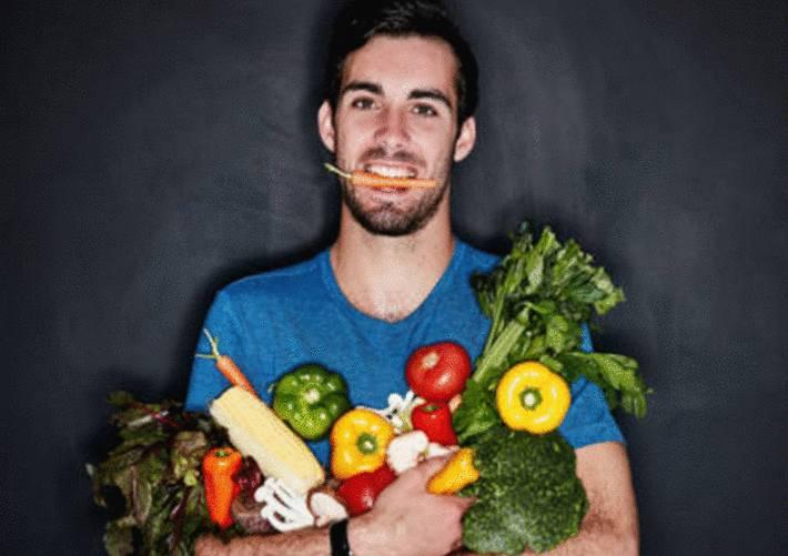 homme-tenant-un-bouquet-de-légumes-avec-une-carotte-entre-les-dents