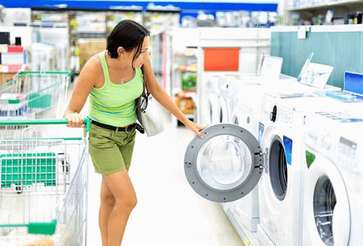 femme-brune-ouvrant-un-hublot-de-lave-linge-dans-un-rayon-de-cinq-lave-linge-en-magasin