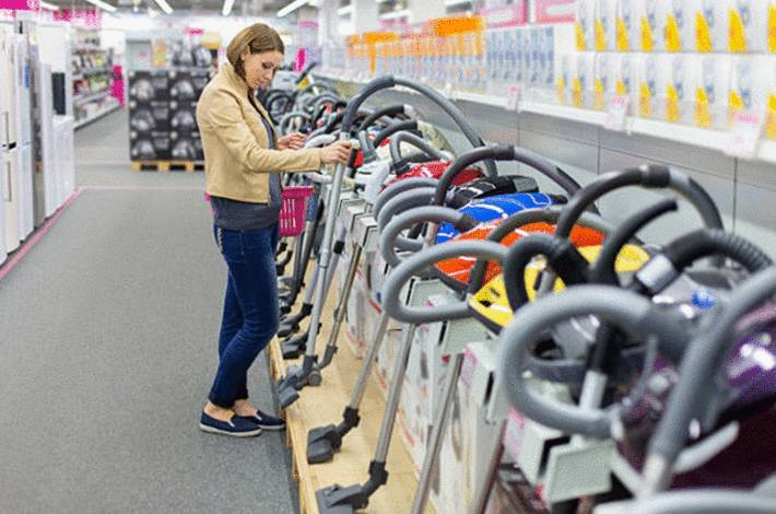 jeune-femme-brune-aux-cheveux-mi-longs-examinant-un-aspirateur-dans-un-magasin-dans-une-rangée-d-aspirateurs