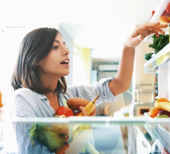 jeune-femme-brune-choisissant-des-légumes-dans-la-porte-du-réfrigérateur