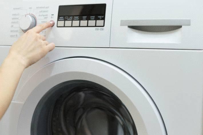 main-de-femme-allumant-un-sèche-linge-avec-écran