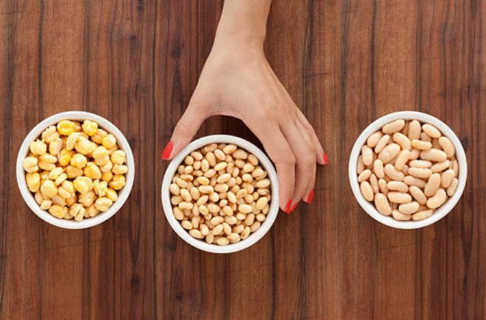 main-de-femme-devant-3-bols-blancs-de-pois-chiches-haricots-secs-fèves