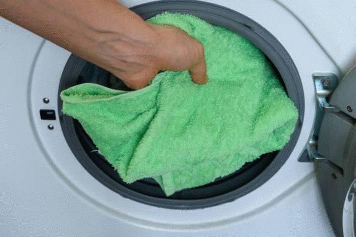 main-insérant-une-serviette-verte-dans-un-sèche-linge-frontal-qui-s'-ouvre-par-devant