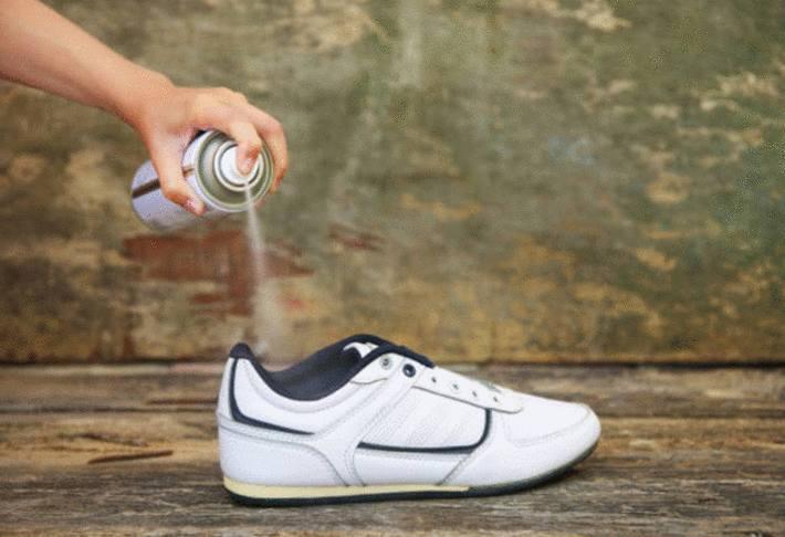 main-vaporisant-du-spray-anti-fongique-au-dessus-d-une-chaussure