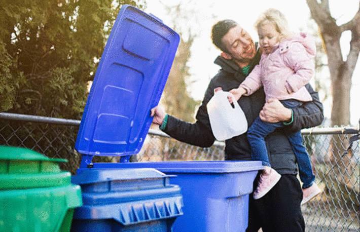 fillette-blonde-jetant-une-bouteille-en-plastique-dans-une-poubelle-bleue-portée-par-son-père