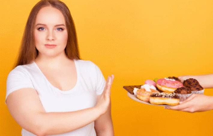 au régime une jeune femme refuse des gateaux